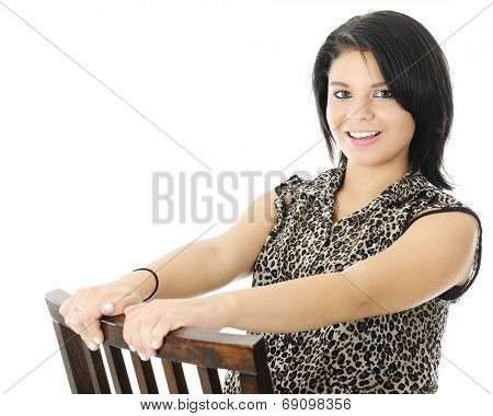 A beautiful teen girl happily holding on as she sits and leans backwards on a wooden chair.  On a white background.