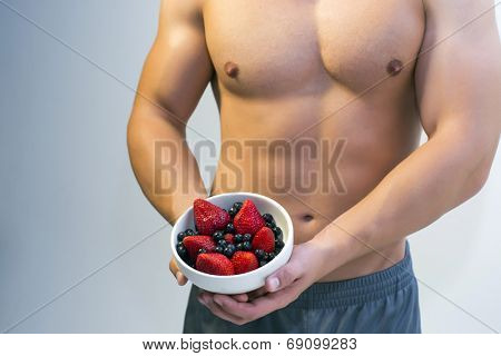 Young fitted man holding a bowl of berries against his nude torso