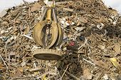 image of junk-yard  - Large tracked excavator working a steel pile at a metal recycle yard with a magnet - JPG