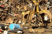 stock photo of junk-yard  - Large tracked excavator working a steel pile at a metal recycle yard with a magnet - JPG