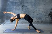 picture of yoga mat  - Woman practicing advanced yoga against a dark texturized wall - JPG