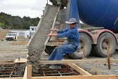 foto of foundation  - Builder directing wet concrete into foundations of a large building