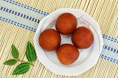 stock photo of jamun  - Gulab jamun dessert on bamboo mat - JPG