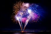 image of firework display  - Colorful fireworks on a beach at midnight - JPG