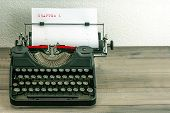 picture of typewriter  - typewriter with white paper page on wooden table - JPG
