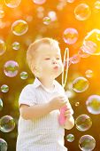 stock photo of blowing  - Child blowing a soap bubbles - JPG