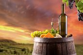 pic of keg  - Wine still life on wooden keg with vineyard on background - JPG