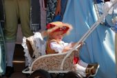 Child In Medieval Clothes Sitting In A Baby Carriage