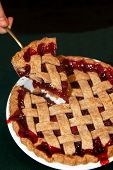 stock photo of cherry pie  - One slice of a whole cherry pie with lattice crust being served - JPG