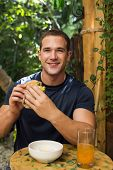 pic of bagel  - Young fitted man enjoying an organic bagel and juice in a raw restaurant - JPG
