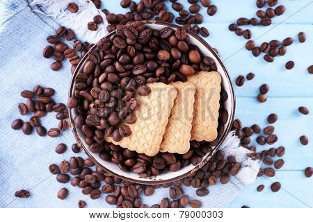Bowl of shortbread cookies and coffee beans on blue wooden background with jeans material