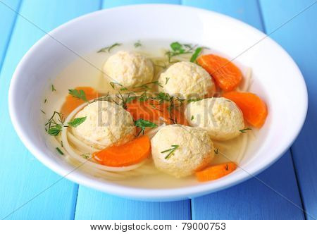Soup with meatballs and noodles in bowl on wooden background