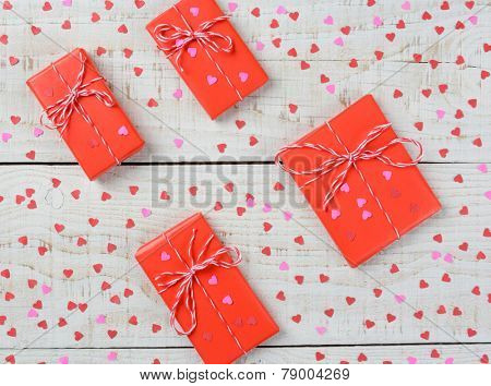 Overhead horizontal shot of a group of Valentines Day presents wrapped in red paper tied with string and surrounded by mini red paper hearts on a rustic wood table.