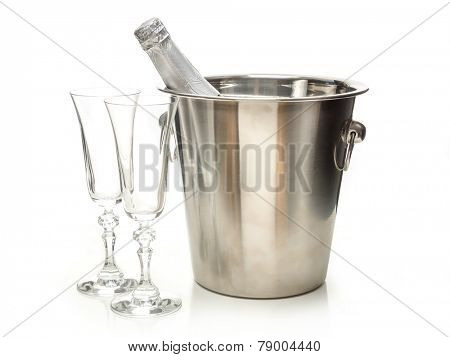 New Year champagne bottle in metal cooler and two champagne glasses shot on white