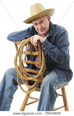 A senior adult cowboy happily sitting backwards on a ladder back chair.  On a white background.