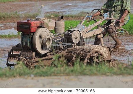 Close up photo of a tractor working in the paddy field in Vietnam