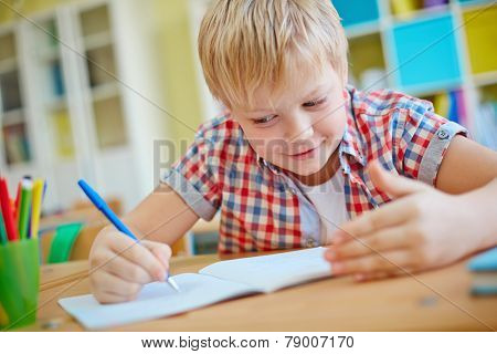 Dishonest schoolboy looking at crib on his palm while writing test
