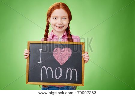 Pretty girl holding board with declaration of love to mother