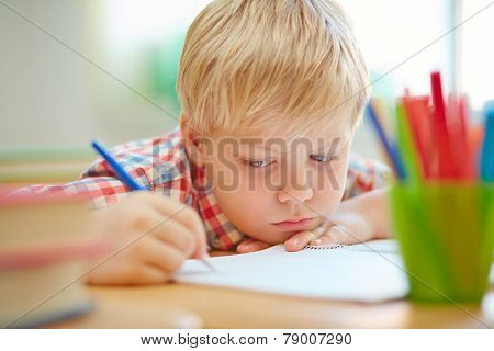 Serious learner making notes or drawing in exercise book