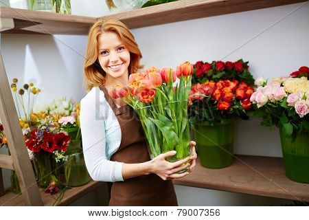 Pretty owner of floral shop looking at camera during work
