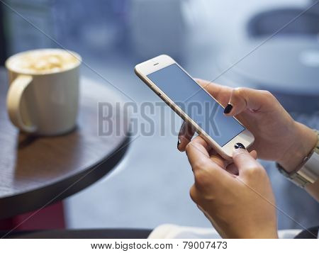 Young Girl Playing Smartphone In Cafe