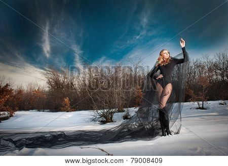 Lovely young lady posing dramatically with long black veil in winter scenery. Blonde woman in snow
