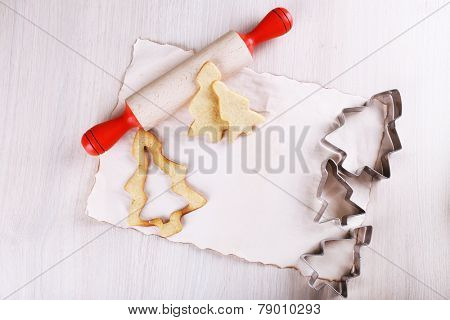 Gingerbread cookies with copper cookie cutter and rolling pin on wooden table background