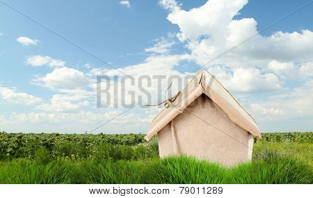 Kraft paper house on green grass in field