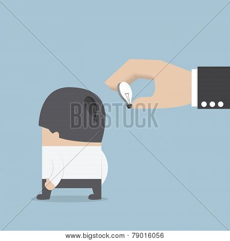 Hand Holding Light Bulb Of Idea And Input It Into Businessman Head