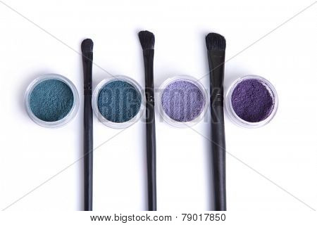 Top view of mineral eye shadows in pastel colors and brushes, isolated on white background