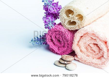 Spa towels rolls flower and stones lying on shite background. Space for your text. Horizontal composition.