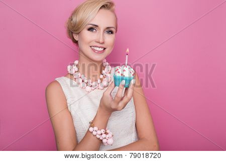 Beautiful young women holding small cake with colorful candle. Birthday, holiday