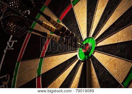 Success hitting target aim goal achievement concept background - three darts in bull's eye close up