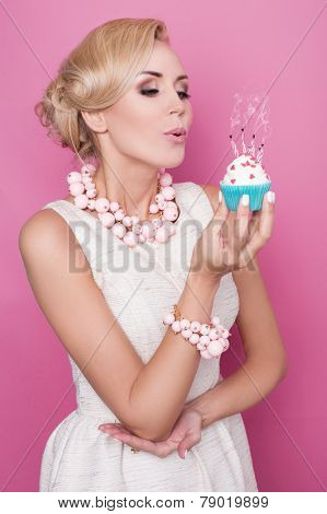 Elegant woman blowing out candles on birthday cake