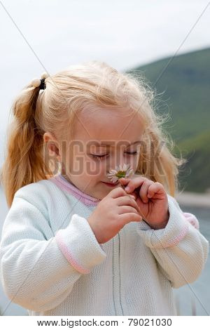 Little Girl Smelling Chamomile
