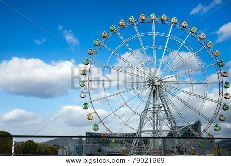 KYOTO, JAPAN - DECEMBER 03, 2014: A ferris-wheel fills the skyline of rural Kyoto. Many shopping centers and amusement parks use the giant ferris-wheel as an attraction  that can be seen from afar.