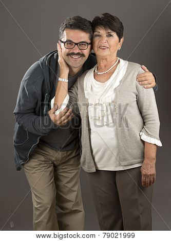 Vertical image of a senior adult woman and her son over gray background.
