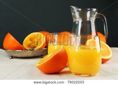 Glass of orange juice with carafe and slices on table and dark background