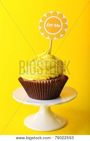 Delicious cupcake with inscription on color background
