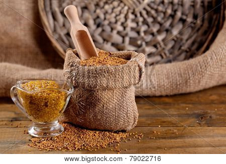 Mustard seeds in bag and sauce in sauce-boat on  wooden background