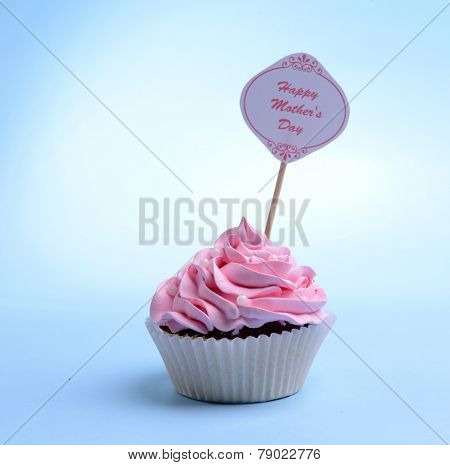 Delicious cupcake with inscription on table on blue background