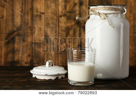 Open milk can on rustic wooden background
