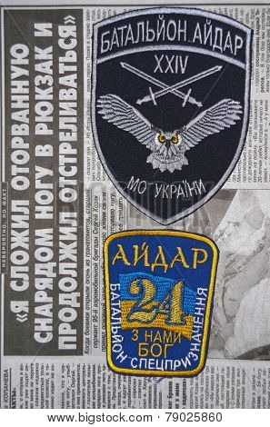 Kiev,Ukraine.Oct 16.Illustrative editorial.Pro-Ukrainian nationalist formations Aidar chevrone .Newspaper with heroic story of soldier as background.At October 16,2014 in Kiev, Ukraine