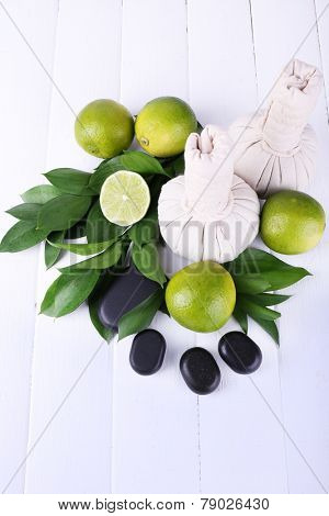 Spa composition with lime and compress balls on color wooden background
