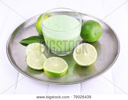 Glass of fresh lime juice with pieces of lime on metal tray on wooden surface background