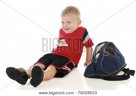 A young preschooler happily relaxed by his sport bag.  On a white background.