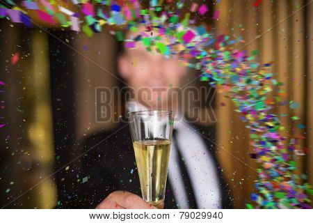Handsome man holding flute of champagne against colour curve