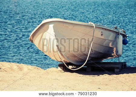 White Rowboat Stands On The Sandy Coast