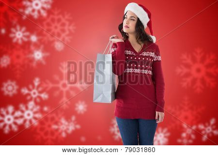 Thoughful brunette in santa hat holding shopping bag against blurred christmas background