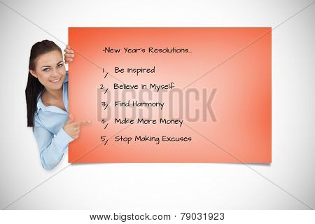 Smiling businesswoman looking around the corner while pointing against orange card